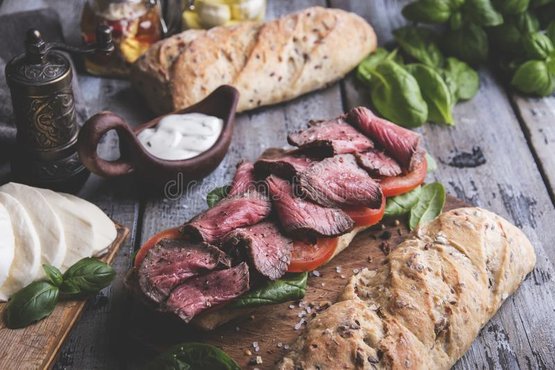 Steak sandwich, sliced roast beef, cheese,spinach leaves,tomato. A stock image