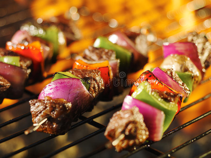 Steak shishkabob skewers cooking on flaming grill stock photography