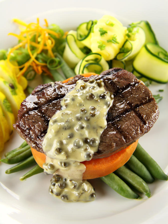 Steak And Sweet Potato. Chargrilled steak on sweet potato with green peppercorn sauce stock photo