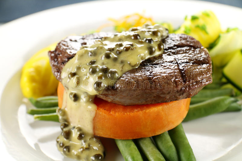 Steak On Sweet Potato. Chargrilled steak on sweet potato with green peppercorn sauce stock photo