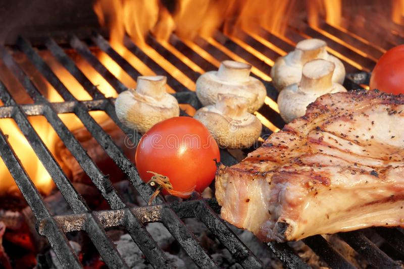 Steak and Vegetables Char-Grilled Over Flaming BBQ Grill royalty free stock images