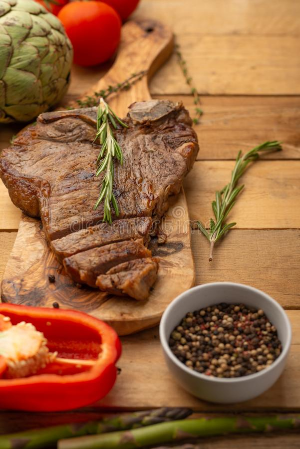 Steak with vegetables on a wooden background, restaurant and hotel business, menu, homemade recipes, culinary background, vertical royalty free stock image