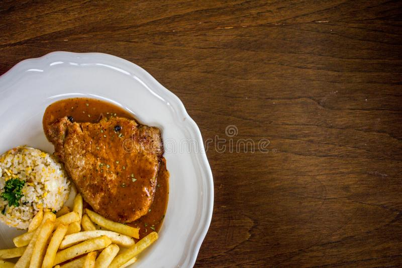 Steak with white plate on wooden table stock photo