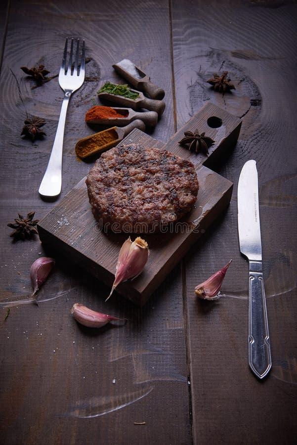 Steakgrill, Lebensmittelhintergrund, hölzerner Hintergrund lizenzfreie stockbilder
