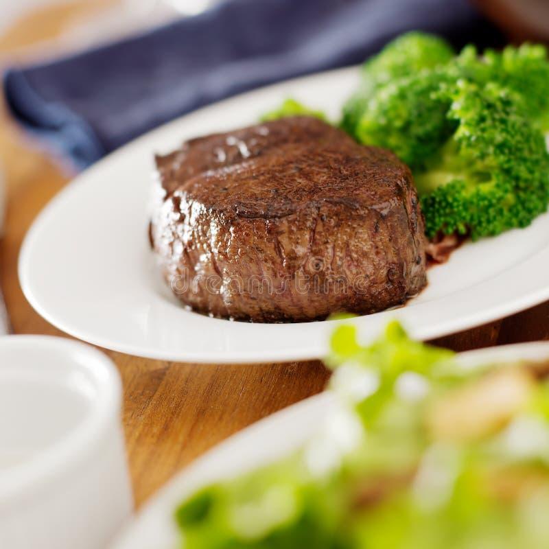 Steakmatställe med sallad och broccoli. arkivbilder