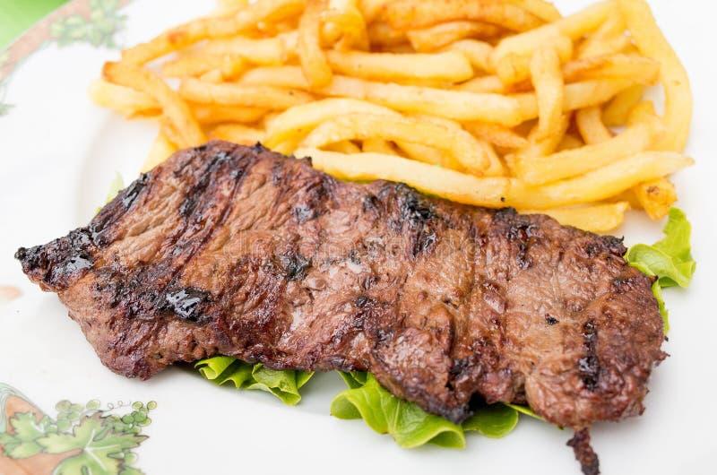 Steakrindfleischfleisch mit Tomate und Pommes-Frites lizenzfreies stockfoto
