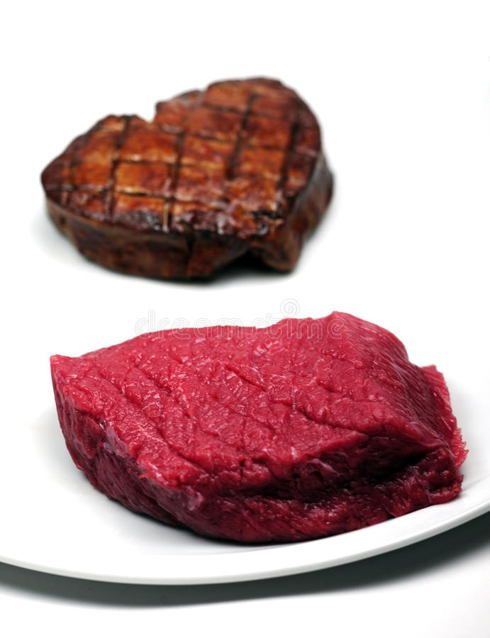 Steaks. A raw steak and a grilled steak royalty free stock photography