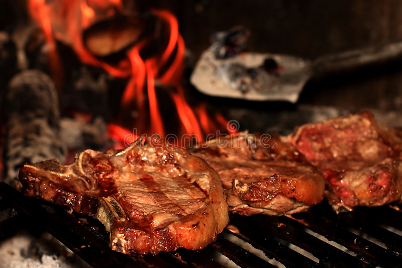 Steaks on the barbecue. Some appetizing steaks on a barbecue with the fire on the background stock image