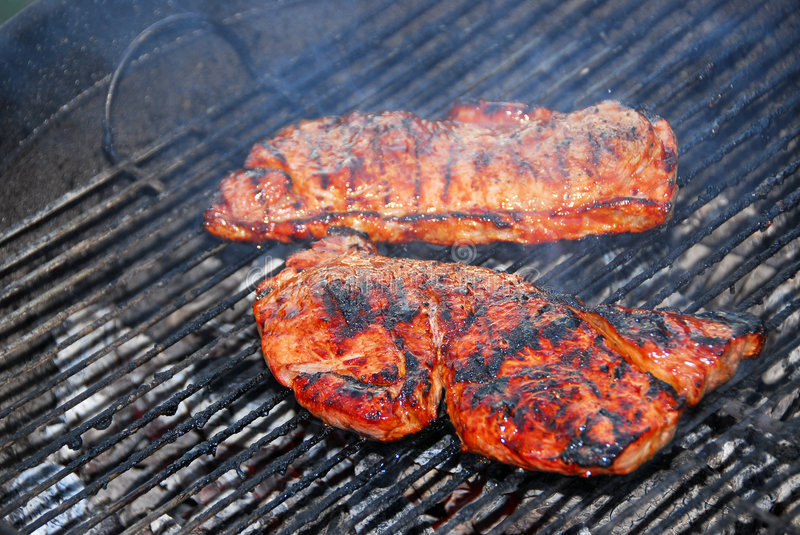 Steaks on barbeque royalty free stock images