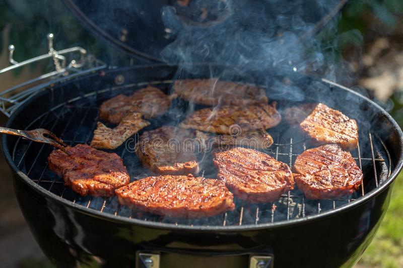 Steaks cooking over flaming grill stock photos