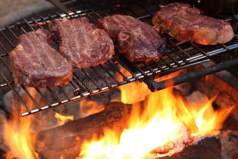 Steaks, die über einem Lagerfeuer kochen lizenzfreie stockbilder