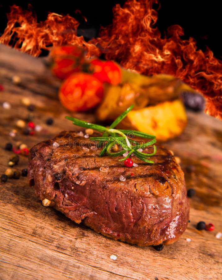 Steaks. Fresh Grilled steaks on wood royalty free stock photography
