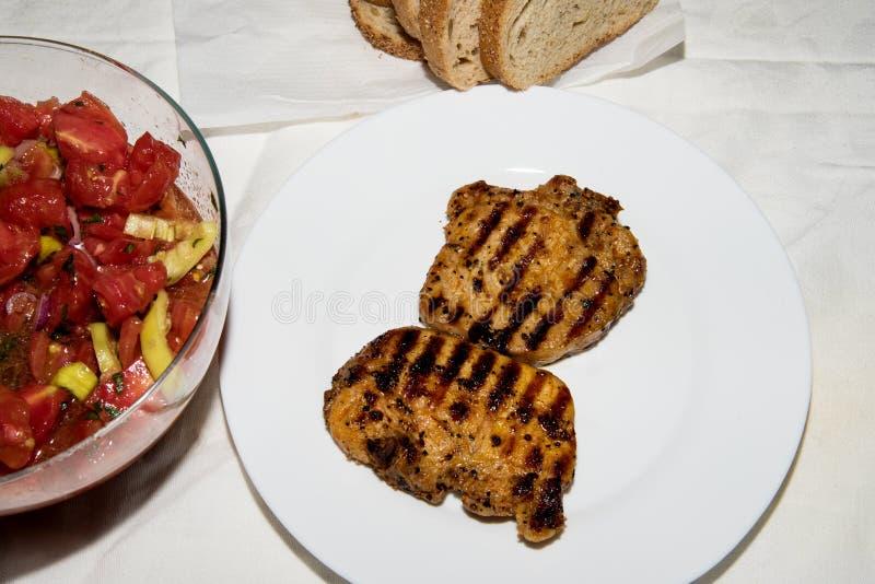 Steaks und Salat mit Tomaten und Gurken für Abendessen stockbilder
