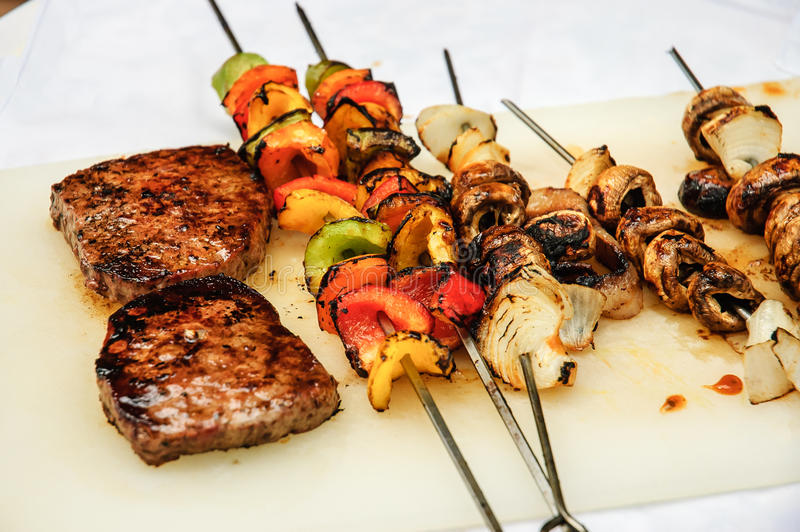 Steaks and vegetables on BBQ royalty free stock photo