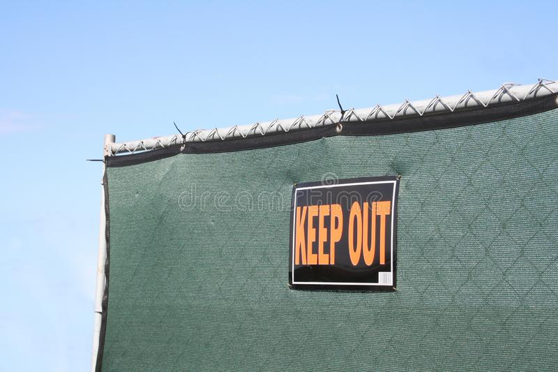 Keep Out Fence. A steal fence covered in green privacy fabric with a KEEP OUT sign posted royalty free stock photos