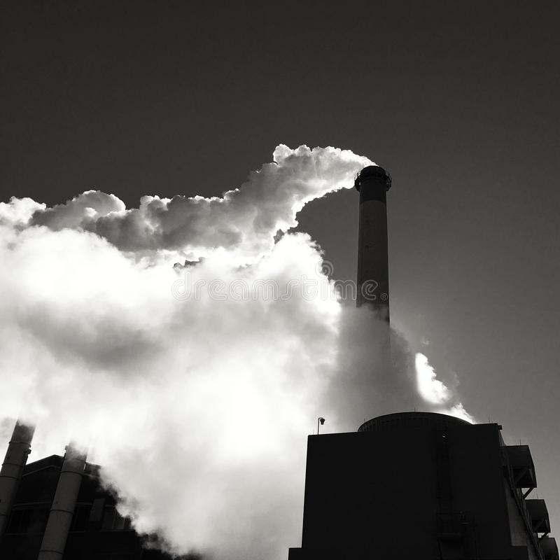Steam billowing from smokestack stock image