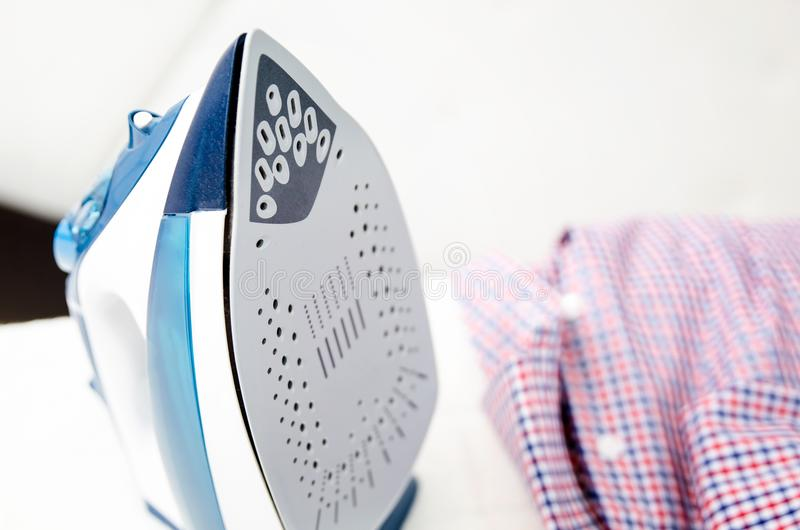 Steam blue iron on ironing board. Clothes, ironing board household concept stock photo
