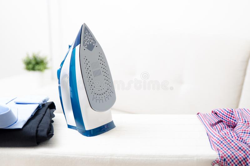 Steam blue iron on ironing board. Clothes, ironing board household concept stock photography