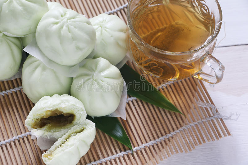 Steam bun with Pandan flavour. Chinese cuisine, steam bun or pau with pandan paste filling served with cup of green tea stock photo
