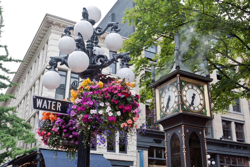 Steam Clock in Gastown Vancouver. A blooming colorful pink, white, yellow and red flower bush on an iron street lamp, the famous steamy Gas Clock and the royalty free stock photography