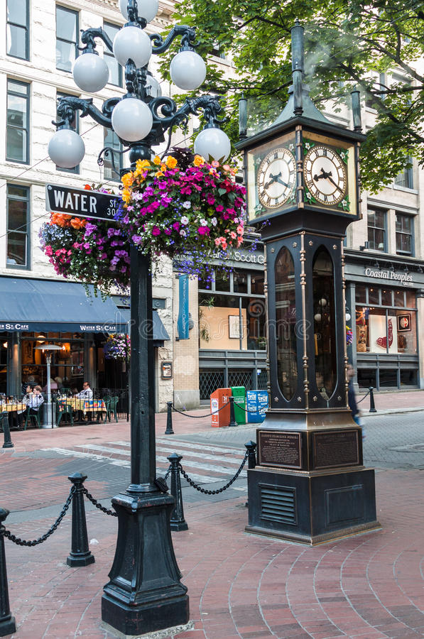 Steam Clock in Gastown Vancouver. A blooming colorful pink, white, yellow and red flower bush on an iron street lamp, the famous steamy Gas Clock and the stock image