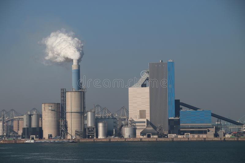 Steam comes out the chimney of the coal power plant of Engie in the Rotterdam Maasvlakte harbor in The Netherlands. Steam comes out the chimney of the coal royalty free stock images