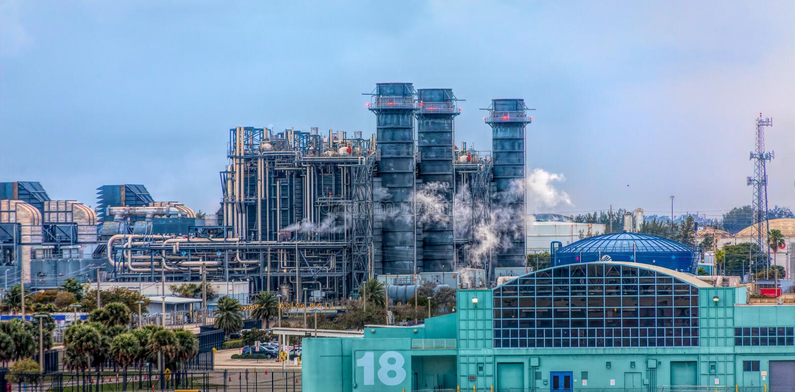 Seaside Industrial Area. Steam coming from Industrial Smokestacks in a busy seaport royalty free stock photos