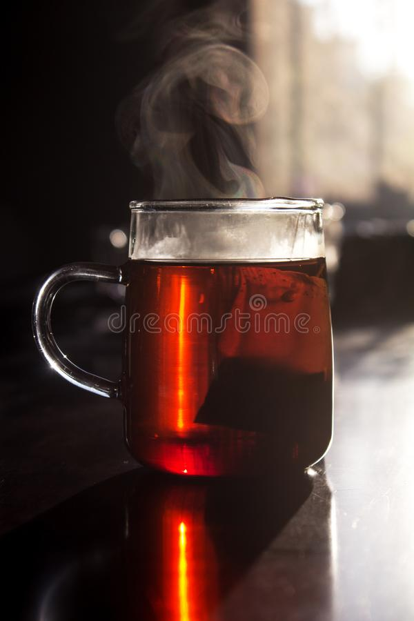 Steam on a cup of tea under morning sun. Morning sun falls on steam rising from a glass cup of tea with teabag inside on wooden table. The glass of tea has a royalty free stock image
