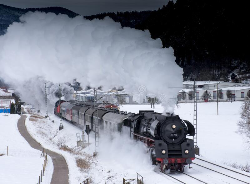 Steam engine train on snowy tracks stock photo