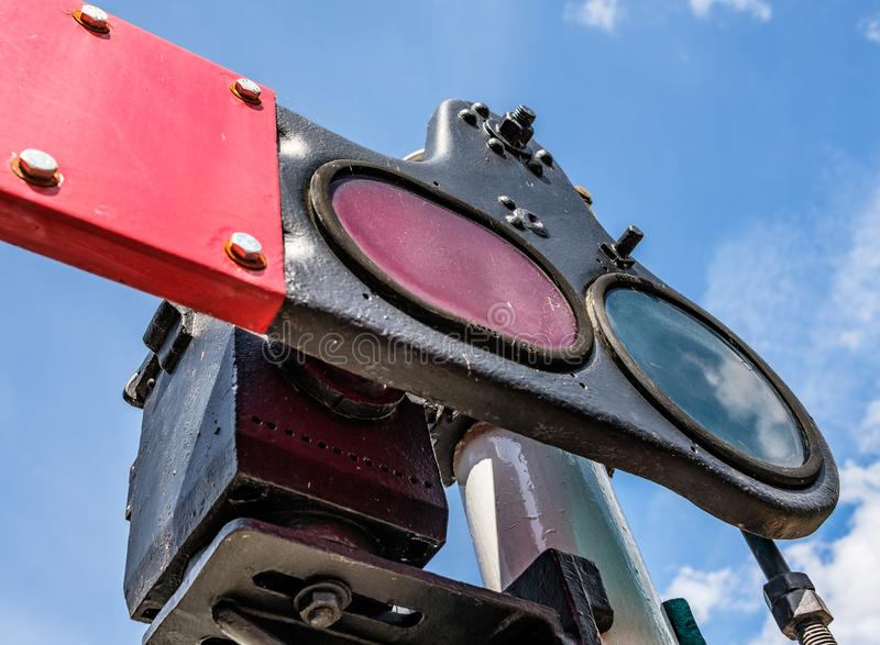 Steam era railway signals seen at a railway junction in the UK. This bygone, steam era signal shows the detail of the motor, glass lenses and red paddle used to stock image