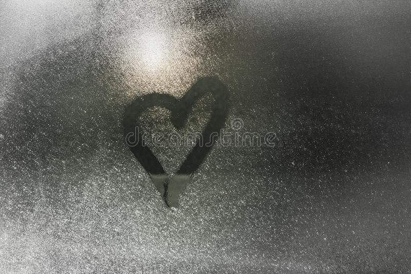 Steam heart painted blurred on a wet window vaporized glass surface stock photos
