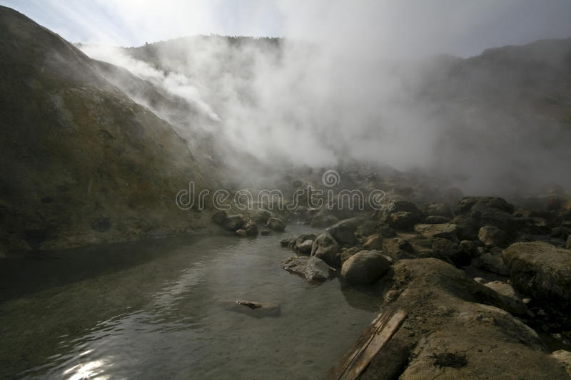 Steam of the hot spring. Hot sprimg with boiling water on the volcano stock image