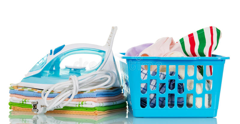 Steam iron, pile towels and plastic basket with clothes isolated. stock photos