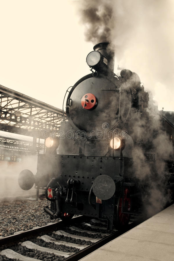 Steam locomotive. At the railway station wrapped up in cloud - vintage retro tinting royalty free stock photos
