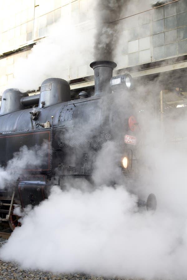 Steam locomotive. At the railway station - historical method of transportation stock image