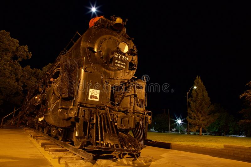 Steam locomotive at night. An antique steam locomotive on display in a park in Kingman, Arizona. Timed exposure, taken at night with ambient lighting makes for a stock photo