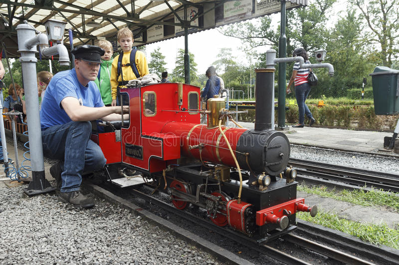Steam miniature train repairer. Steam miniature train driver preparing the locomotive for an imminent departure royalty free stock photography