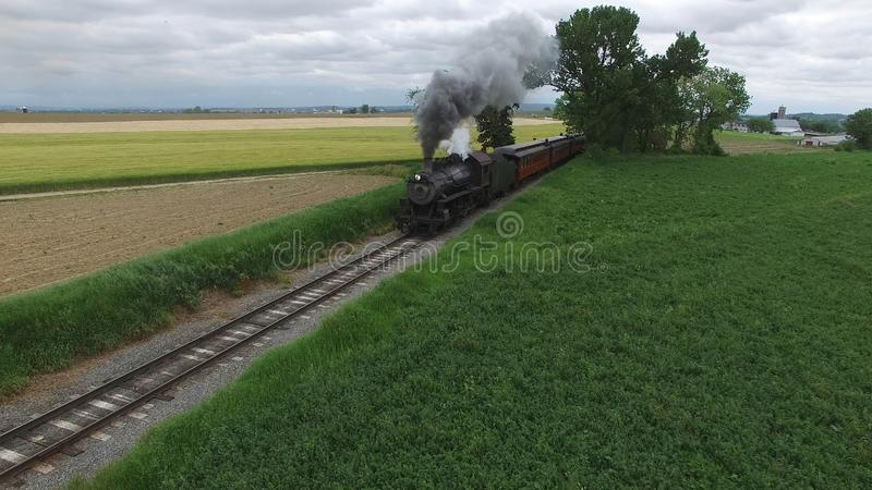 Steam Passenger Train Puffing Smoke in amish Countryside 2. Aerial View of a Steam Passenger Train Puffing Smoke in Amish Countryside on a Sunny Spring Day stock photos