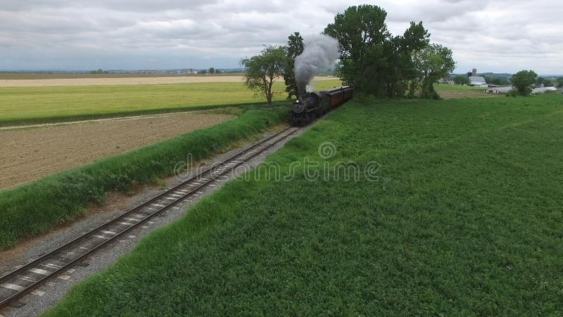 Steam Passenger Train Puffing Smoke in amish Countryside 1. Aerial View of a Steam Passenger Train Puffing Smoke in Amish Countryside on a Sunny Spring Day stock photos