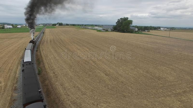 Steam Passenger Train Puffing Smoke in amish Countryside 6. Aerial View of a Steam Passenger Train Puffing Smoke in Amish Countryside on a Sunny Spring Day royalty free stock image