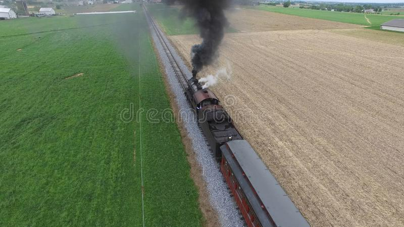Steam Passenger Train Puffing Smoke in amish Countryside 11. Aerial View of a Steam Passenger Train Puffing Smoke in Amish Countryside on a Sunny Spring Day stock image