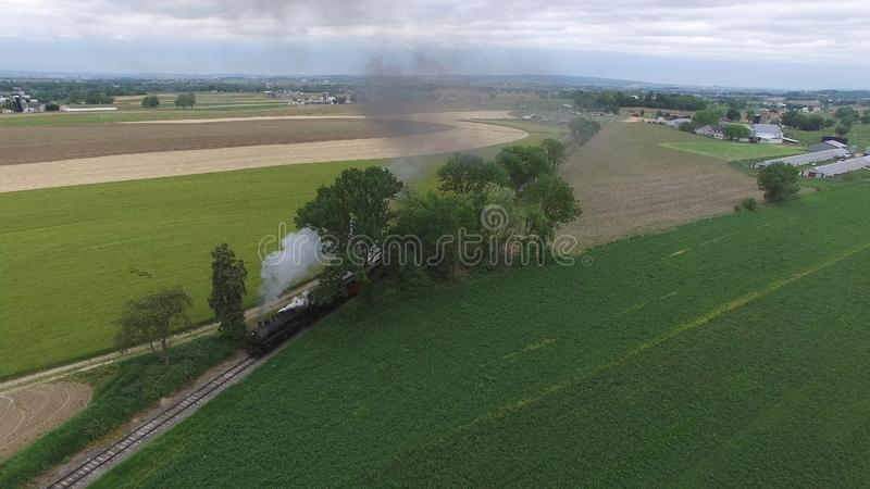 Steam Passenger Train Puffing Smoke in amish Countryside 15. Aerial View of a Steam Passenger Train Puffing Smoke in Amish Countryside on a Sunny Spring Day stock photos