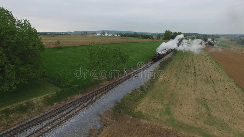 Steam Passenger Train Puffing Smoke in amish Countryside 24. Aerial View of a Steam Passenger Train Puffing Smoke in Amish Countryside on a Sunny Spring Day royalty free stock photos