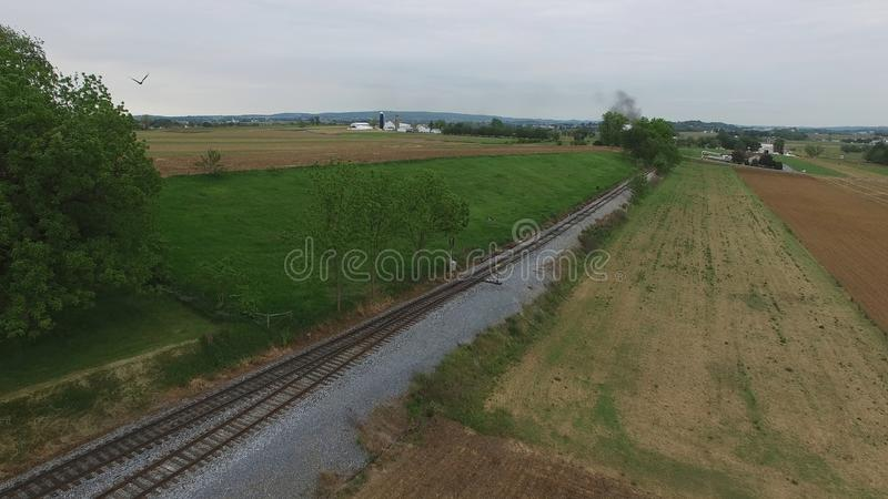 Steam Passenger Train Puffing Smoke in amish Countryside 22. Aerial View of a Steam Passenger Train Puffing Smoke in Amish Countryside on a Sunny Spring Day stock image