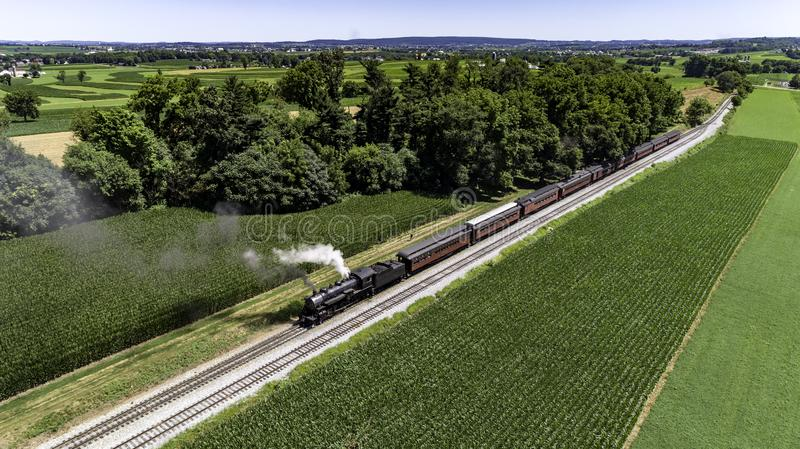 Steam Passenger Train Puffing Smoke in amish Countryside 30. Aerial View of a Steam Passenger Train Puffing Smoke in Amish Countryside on a Sunny Spring Day stock images
