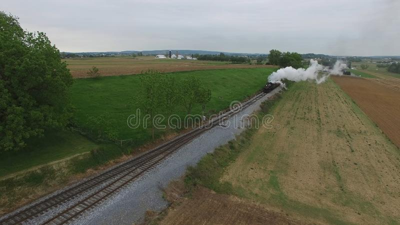 Steam Passenger Train Puffing Smoke in amish Countryside 23. Aerial View of a Steam Passenger Train Puffing Smoke in Amish Countryside on a Sunny Spring Day stock photography