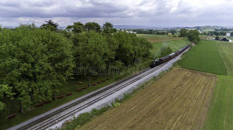Steam Passenger Train Puffing Smoke in amish Countryside 29. Aerial View of a Steam Passenger Train Puffing Smoke in Amish Countryside on a Sunny Spring Day stock image