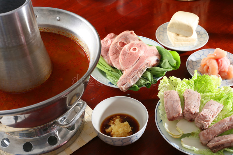 Steam-pot. Set-up of the steam-pot meal with meat, sause and hot spicy soup stock photo