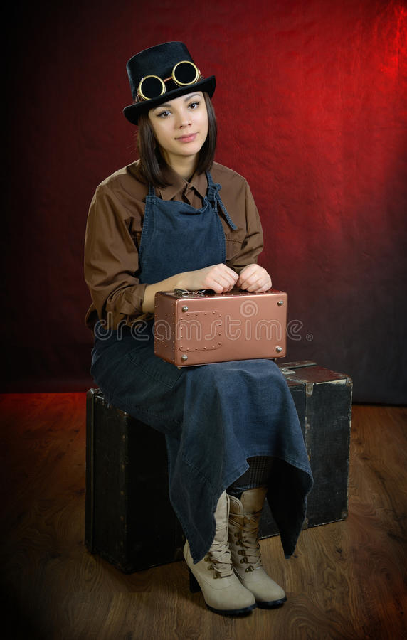Steam punk girl porter sitting on suitcase royalty free stock photography