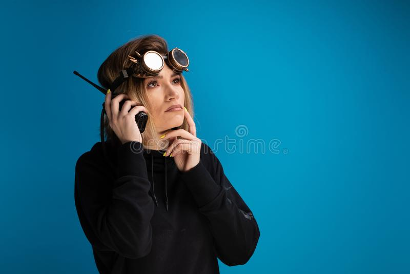 Steam punk girl wearing glasses uses a walkie talkie and poses as thinking stock photography